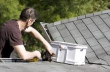 a handyman clears out a gutter